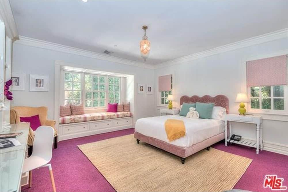 Spacious master bedroom featuring a purple carpet flooring topped by a brown area rug, along with white walls and ceiling. The room has a lovely bed set and a built-in desk on the side.