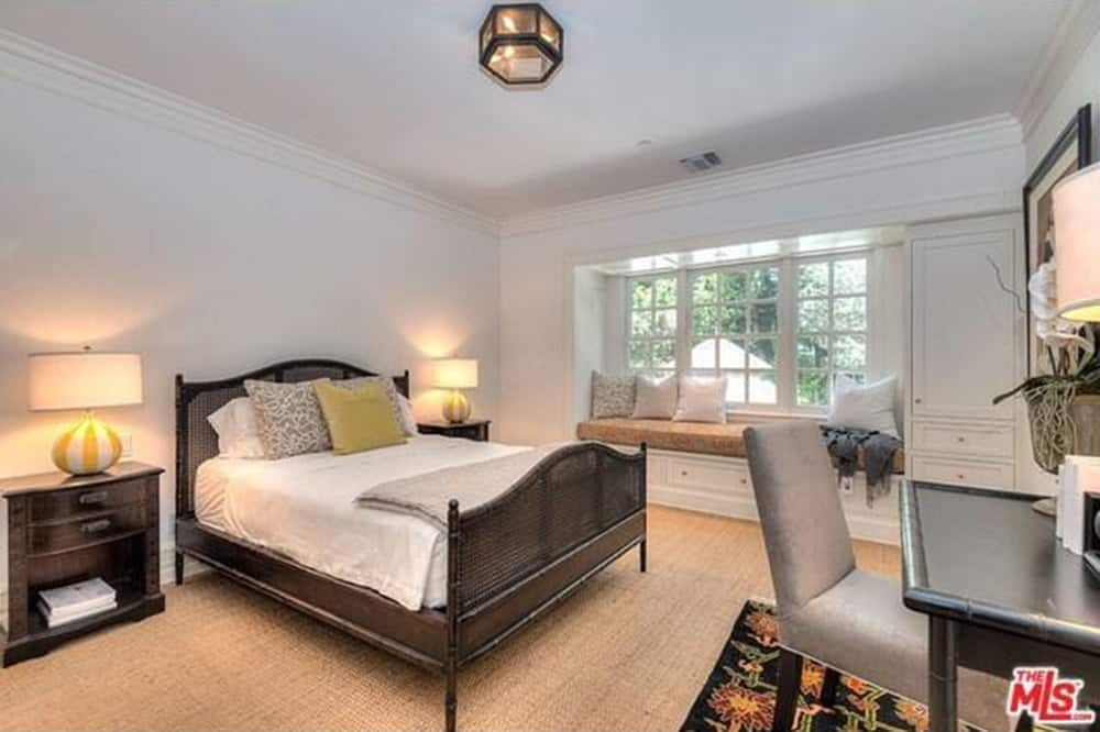 Small master bedroom featuring a bed lighted by table lamps along with a desk lighted by a classy table lamp.