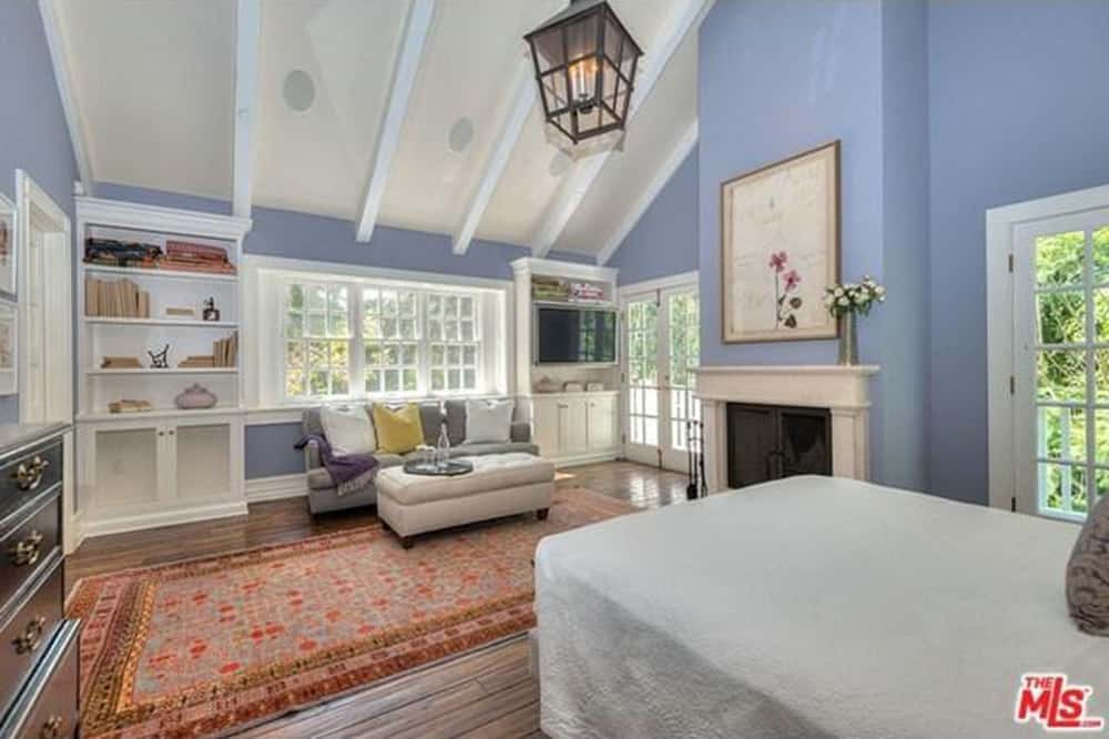 Master bedroom with hardwood flooring topped by an area rug along with a tall ceiling and indigo blue walls. The room offers a nice bed, a small sitting area with a gray couch and a fireplace.