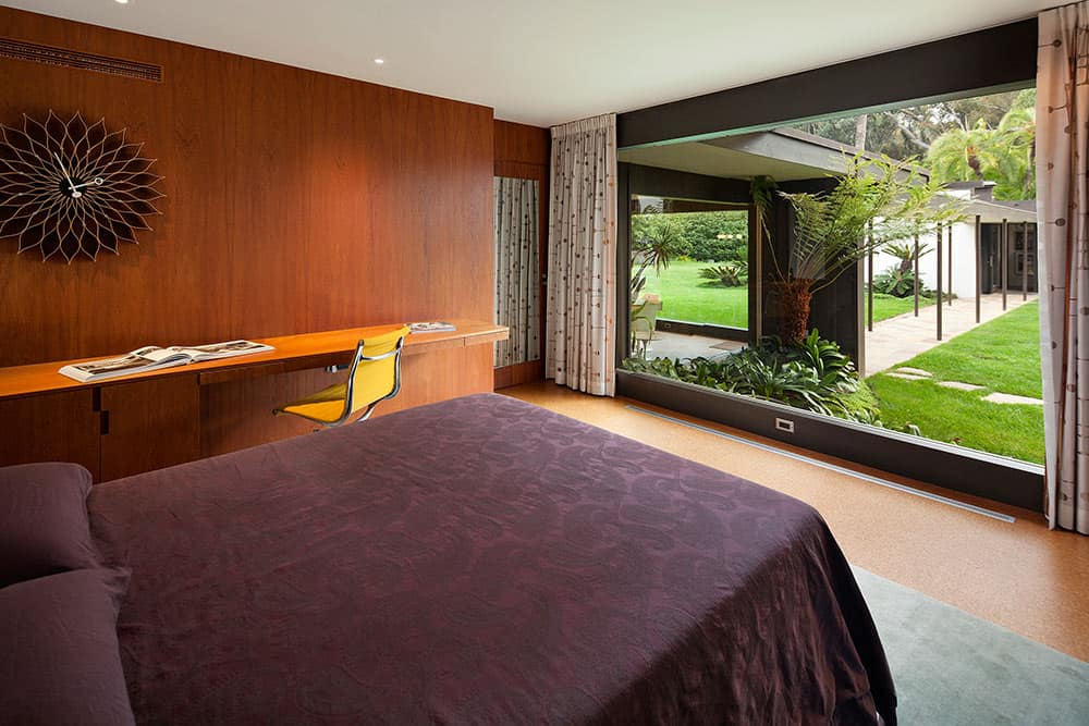 Modern master bedroom with a brown wall and a white ceiling. The room offers a purple desk, a built-in desk and a large glass window overlooking the beautiful garden area.