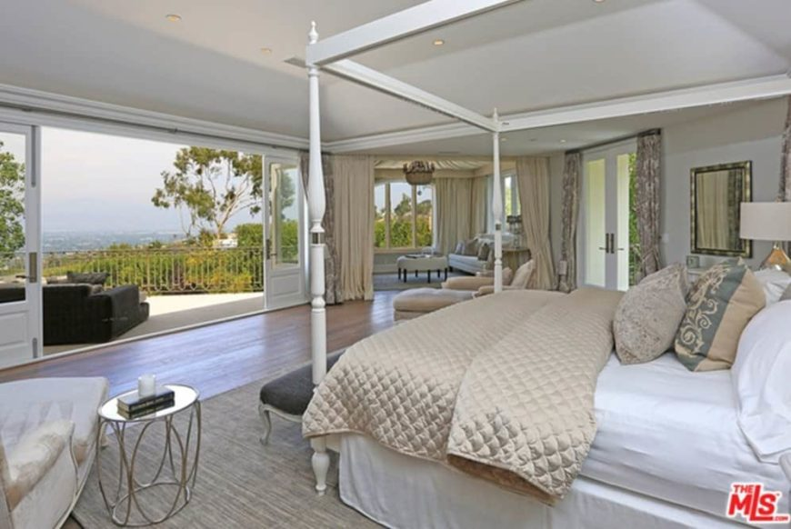 Large master bedroom featuring hardwood flooring and a tray ceiling. It has a large bed and a large private balcony overlooking the stunning surroundings.