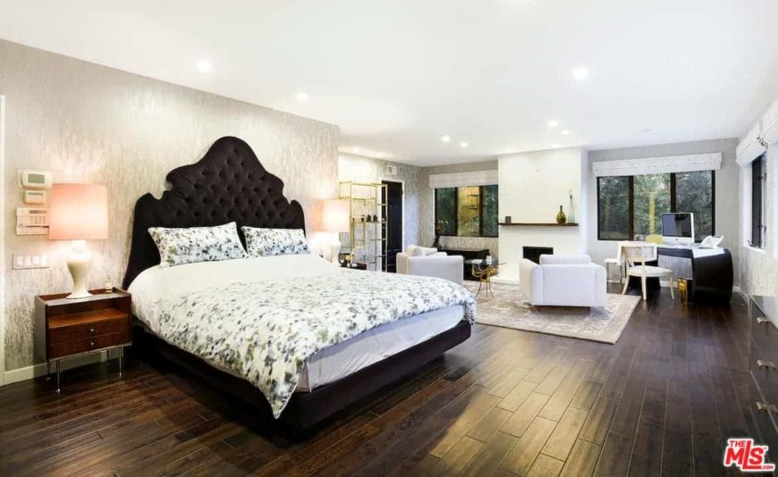 Large master bedroom featuring a gorgeous walls and hardwood flooring, along with a regular white ceiling with recessed ceiling lights. The room has a stylish bed, a personal living space and an office desk area.