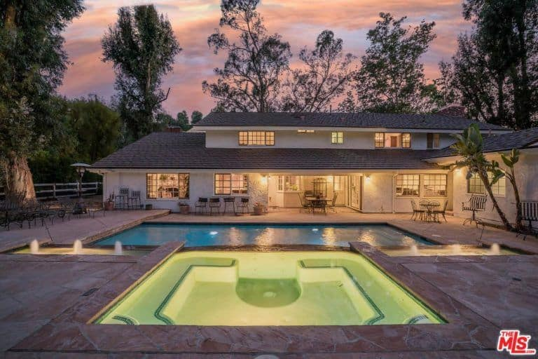 Spacious outdoor area with a rectangular swimming pool along with multiple sitting spots. The home is surrounded by mature trees.