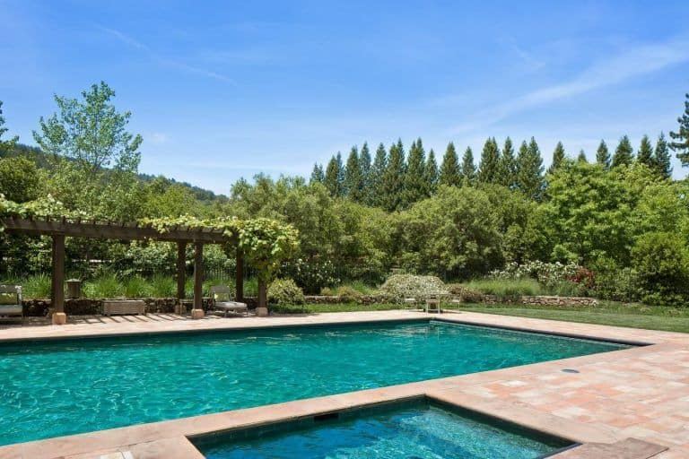A simple rectangular swimming pool set outside of this home, which is surrounded by wide greens area.