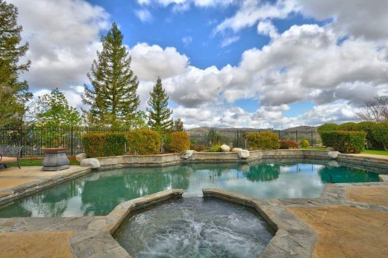 A gorgeous custom-made swimming pool surrounded by beautiful plants and trees. The blue sky is filled with clouds in the background.