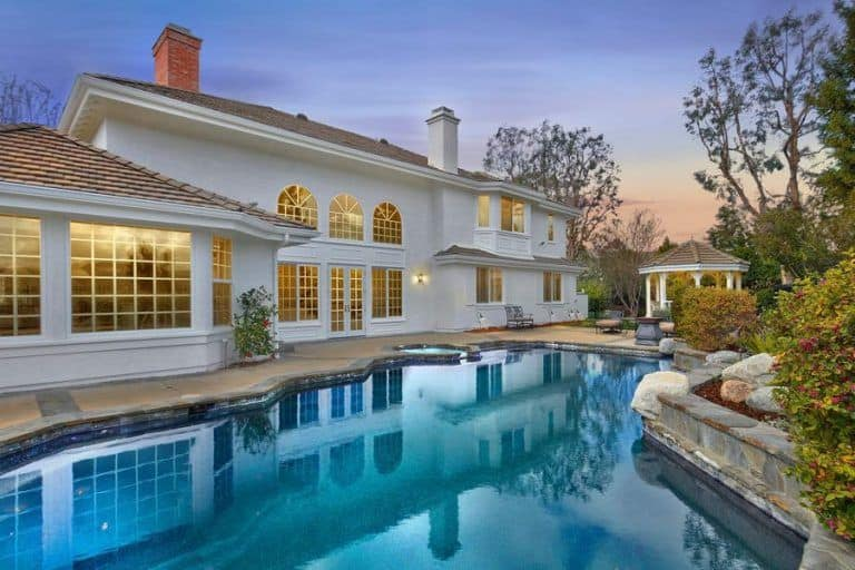 This home boasts a gorgeous custom swimming pool with lovely plants and trees on the side.
