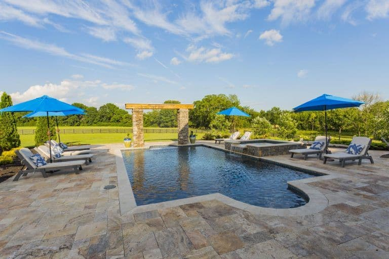 Large outdoor area featuring a Mediterranean swimming pool with sitting lounges on both sides. The area is surrounded by wide lawn area.