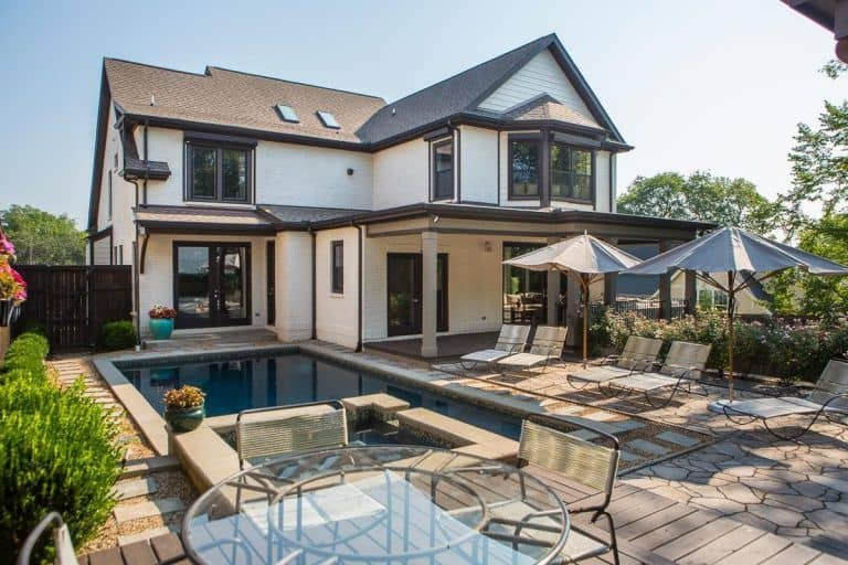 A beautiful house featuring a backyard with a swimming pool and multiple sitting lounges, together with an outdoor dining table set.