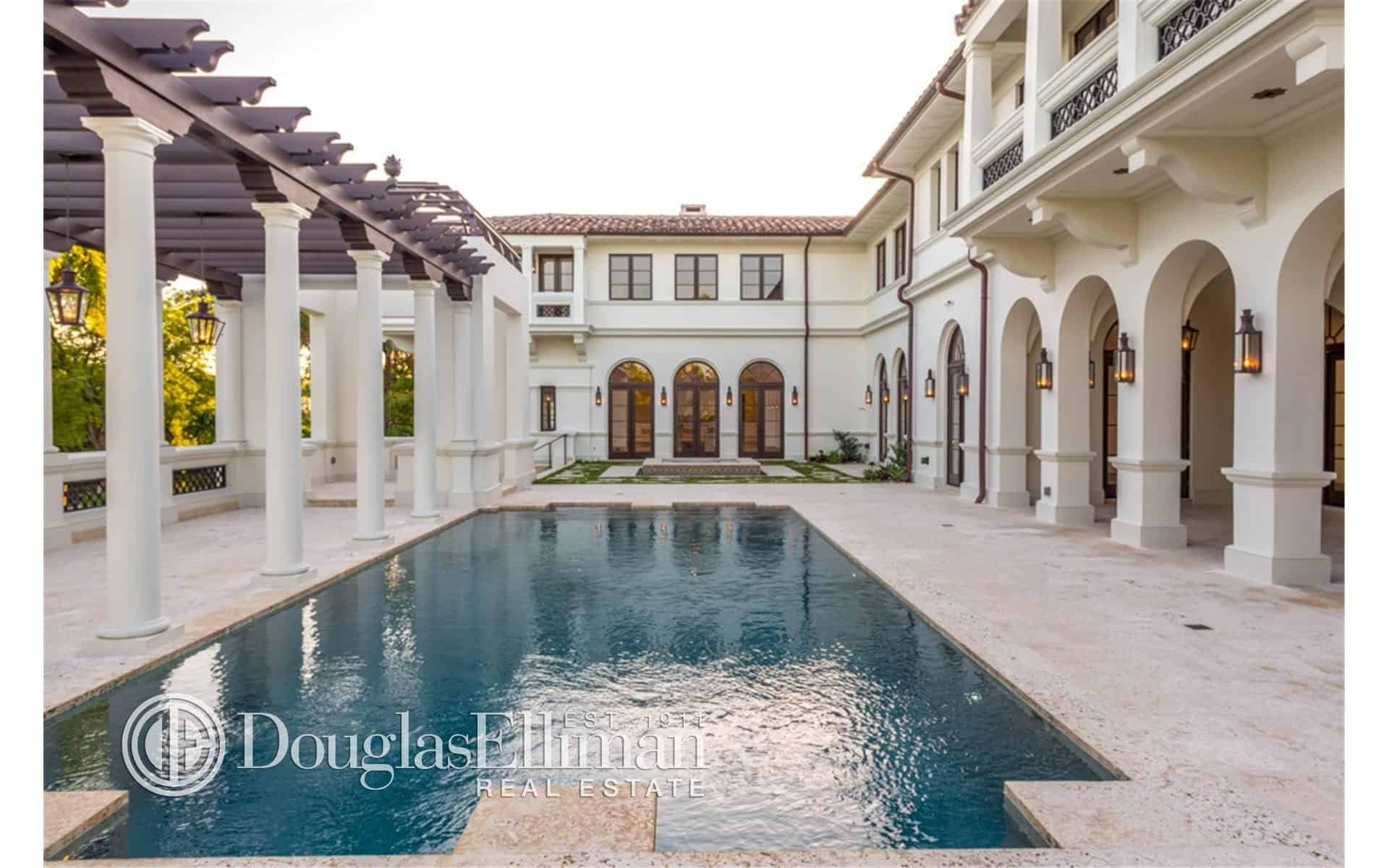 This mansion offers a large custom swimming pool set near the small garden area of the home.