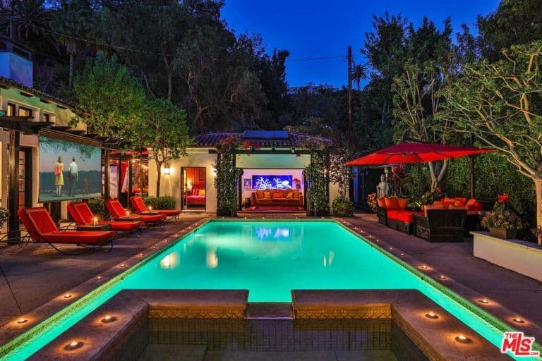 A gorgeous outdoor area boasting red seats and a red patio set with an umbrella, along with a rectangular swimming pool.