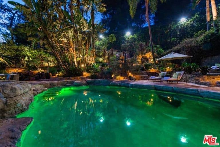 This boasts a stunning custom ceiling with sitting lounges on the side along with large charming trees surroundings the area.