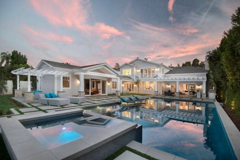 Large outdoor area with a modern swimming pool and lounging seats on the side. The area also has beautiful lawn areas and an outdoor kitchen.
