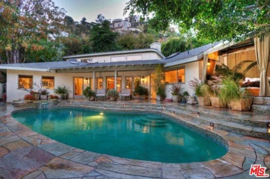 A custom swimming pool set outside of this home, surrounded by green potted plants and mature trees.