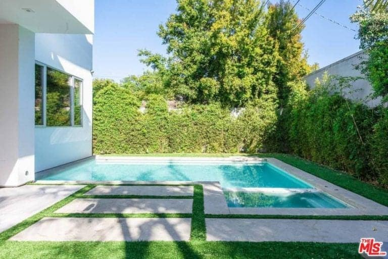 This home features a small backyard with a swimming pool surrounded by green plants and trees. The backyard also has well-maintained lawn and a nice walkway.