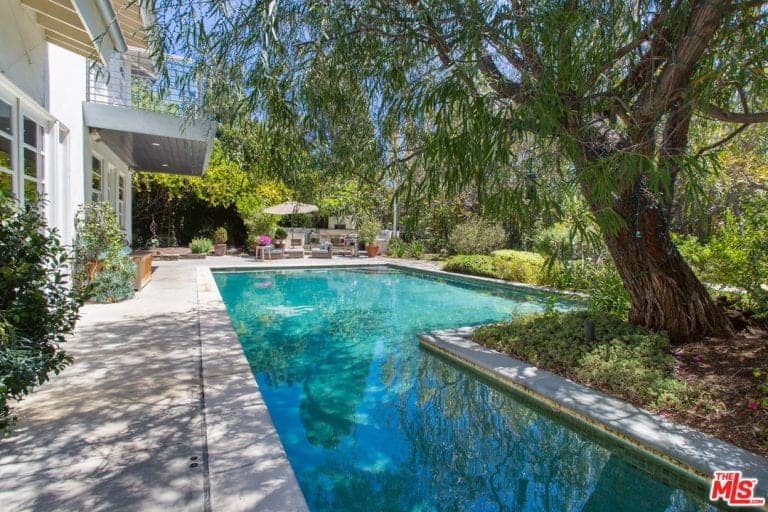 This home boasts a large custom swimming pool surrounded by plants and mature trees. The outdoor area has a patio and other sitting areas.