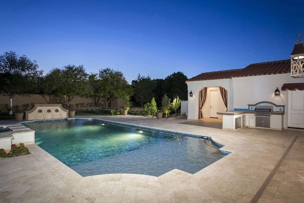 This home offers a stylish swimming pool along with an outdoor kitchen and mature trees surrounding the area.