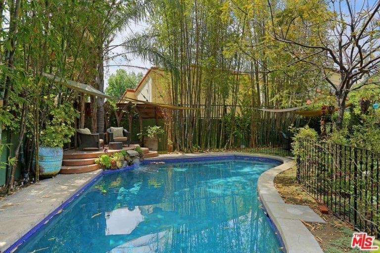 This swimming pool is surrounded by gorgeous mature trees and green plants. There's a sitting area on the side overlooking the beautiful garden.