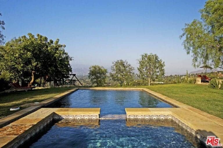 A large outdoor area featuring a stunning swimming pool alongside the property's well-maintained lawn areas.