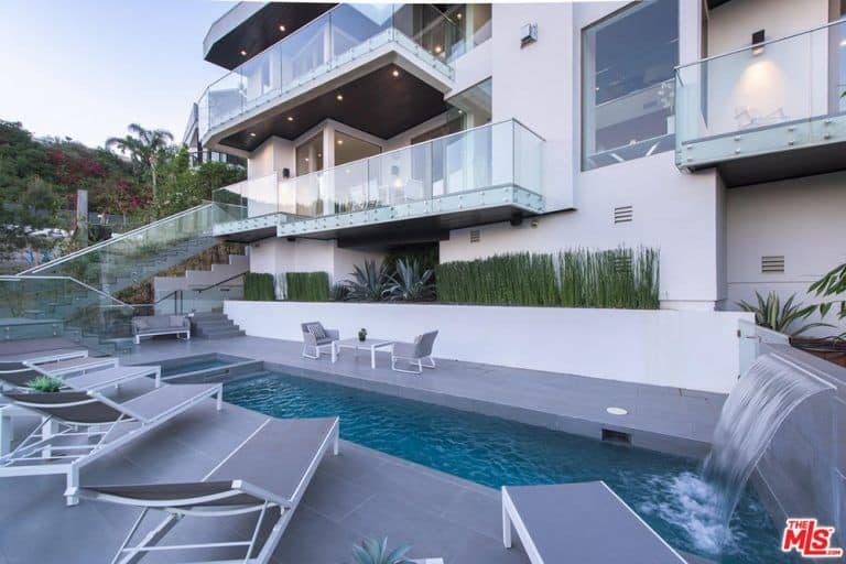 A modern house with a gorgeous outdoor area featuring a modish swimming pool with lounging seats on the side.