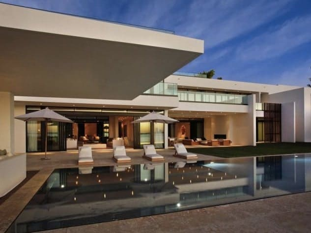 A contemporary house featuring an outdoor area with a modern infinity-style swimming pool, along with relaxing sitting lounges on the side.
