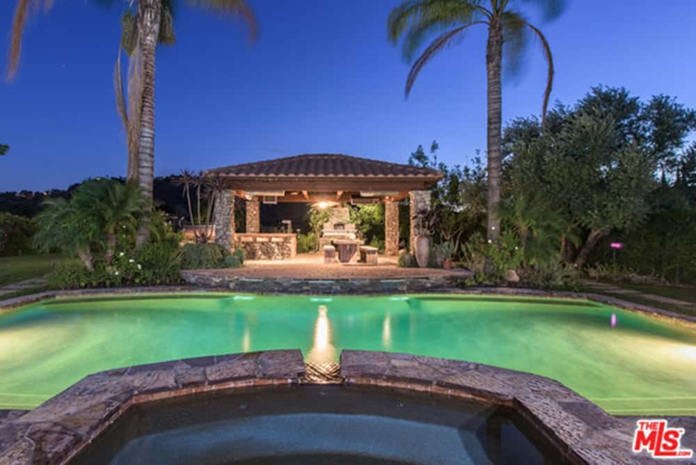 A close up look at this home's large swimming pool surrounded by healthy plants and trees.