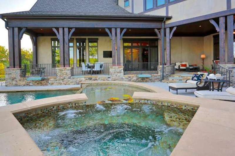 A custom-made swimming pool with a jacuzzi, set outside of this beautiful house.