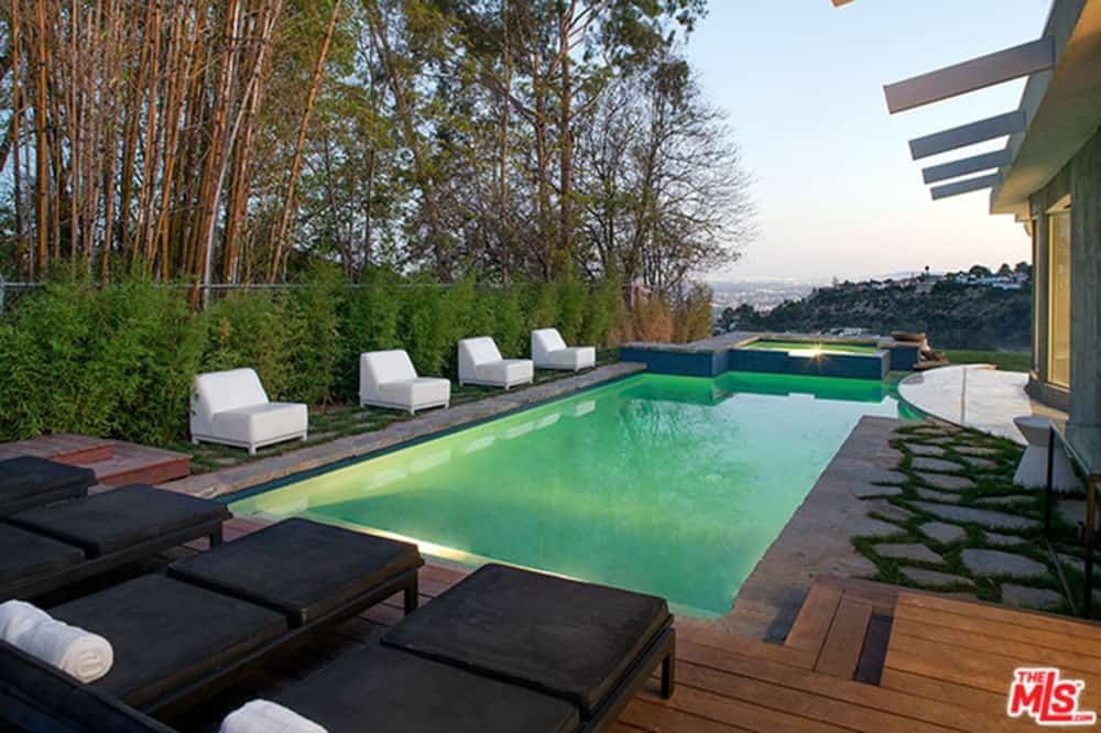 This home offers a modern swimming pool along with black sitting lounges along with white chairs on the side.