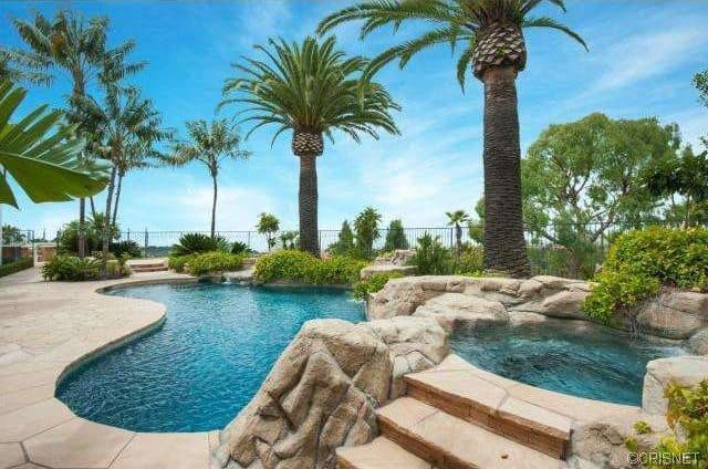 A tropical-style outdoor area featuring a kidney-shaped swimming pool with a custom jacuzzi, surrounded by beautiful mature trees and healthy plants.