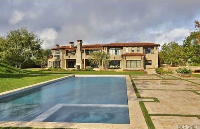 A mansion boasting a large backyard with well-maintained lawn areas and a large rectangular swimming pool.
