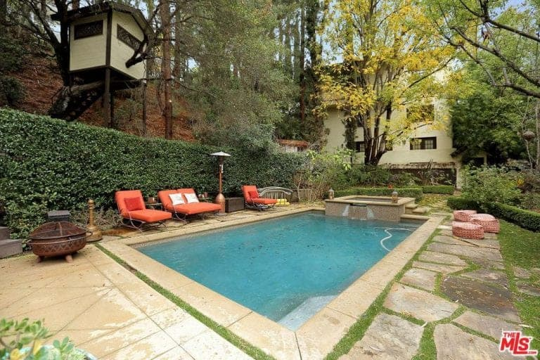 A focused look at this home's outdoor area featuring a rectangular swimming pool with sitting lounges on the side. The area is surrounded by gorgeous plants and trees.