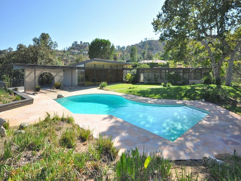 An outdoor custom swimming pool with a lawn area and green plants around it.