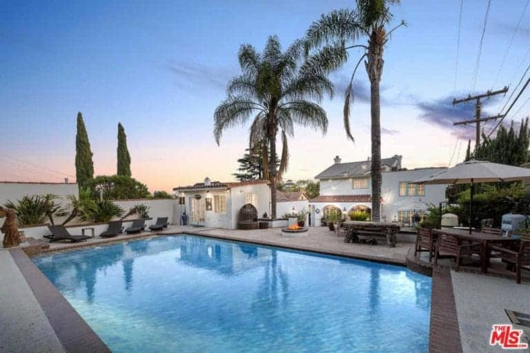 This home boasts a peaceful outdoor area featuring a swimming pool and an outdoor dining area, together with multiple sitting areas.