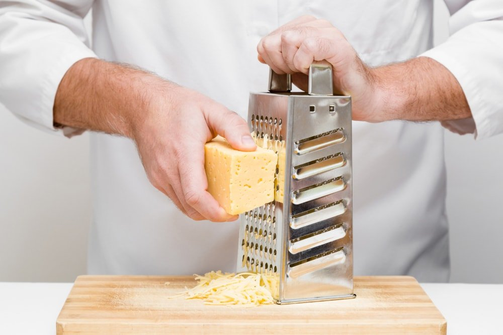 Grating cheese using a steel grater.