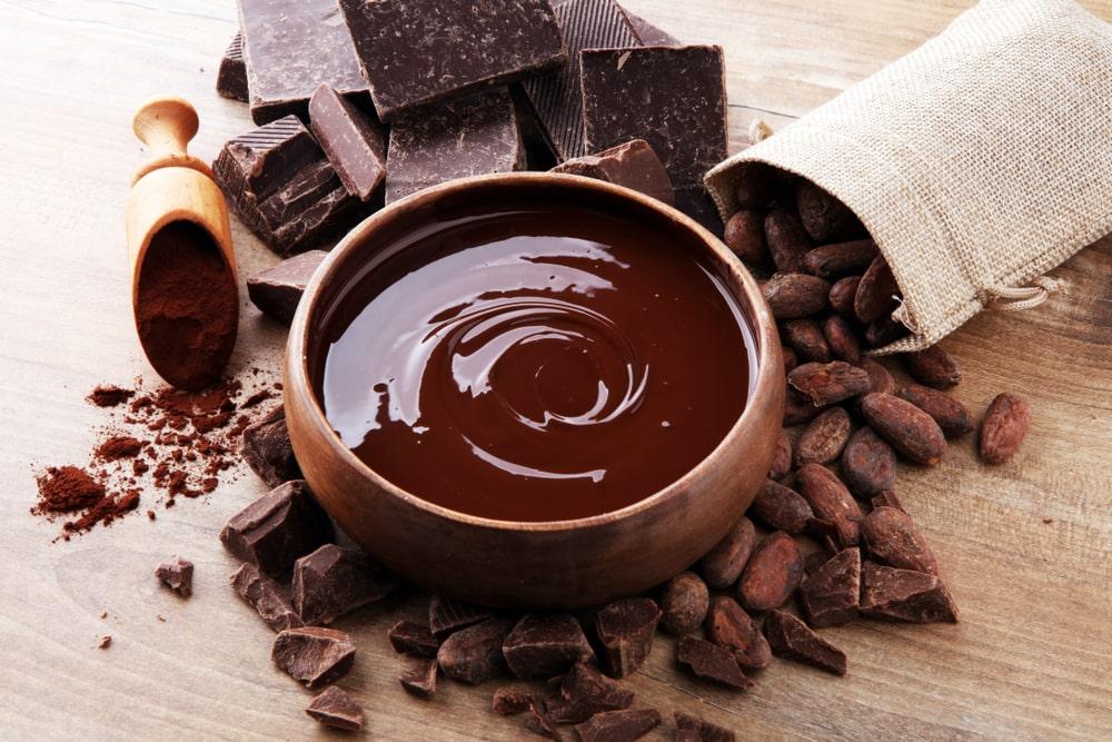 Chocolates surrounding a bowl of chocolate sauce.