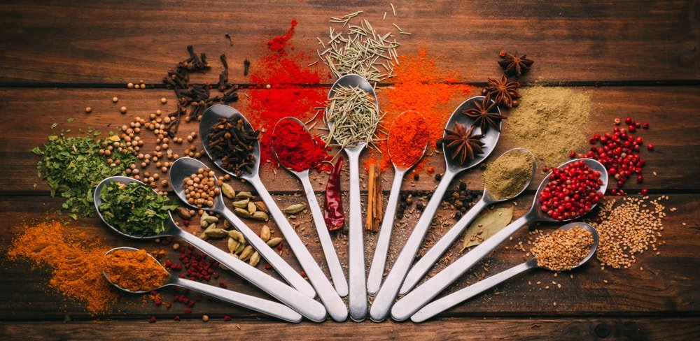 Different types of condiments on spoons against a wooden background.