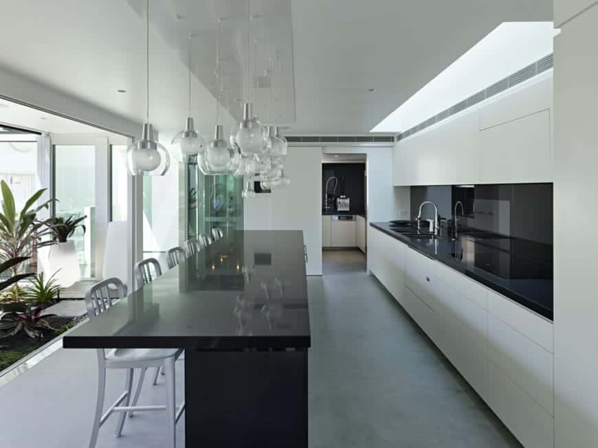 This Cottage-style kitchen has a touch of modern look to its sleek black countertops and white ceiling with a long skylight above the cooking area and faucet area. The black kitchen island is topped with a number of glass pendant lights that elevate the aesthetics of the kitchen.