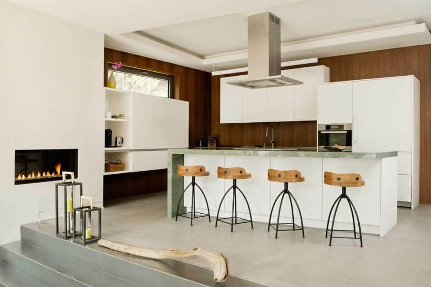 The white cabinetry of this Cottage-style kitchen stands out against the dark wooden walls that bring a nice contrast to the plain tones. The kitchen island in the middle of the light gray floor has a gray marble waterfall countertop paired with four stools.