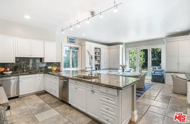 The gray marble tile flooring is a nice complement to the gray marble countertops of the U-shaped peninsula of the Cottage-style kitchen. It also matches well with the stainless steel appliances that contrast the white shaker cabinets and drawers.