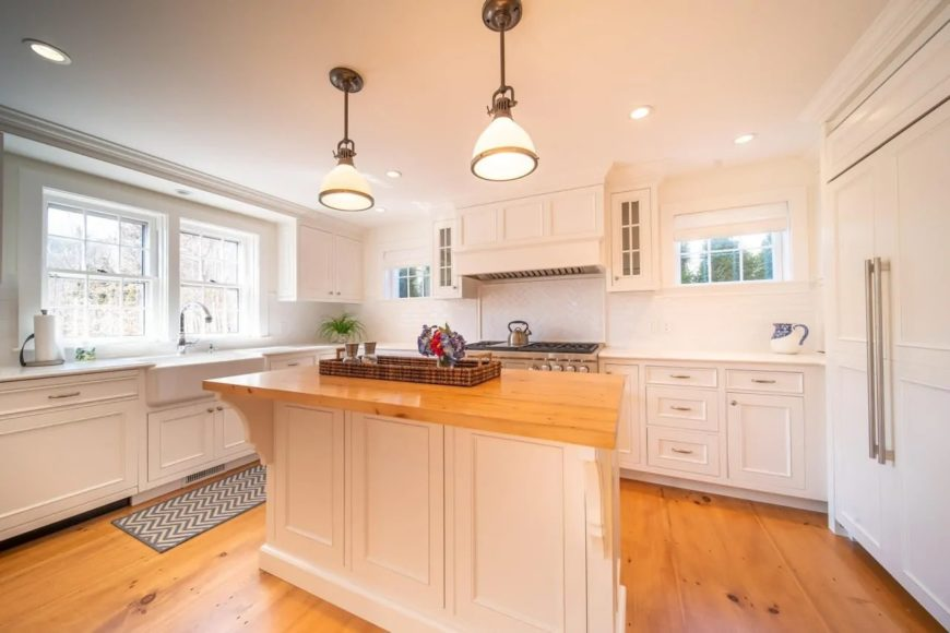 The hardwood flooring of this Cottage-style kitchen matches well with the butcher block countertop of the wooden kitchen island with shaker cabinets. This matches well with the surrounding white cabinetry that blends with the white ceiling.