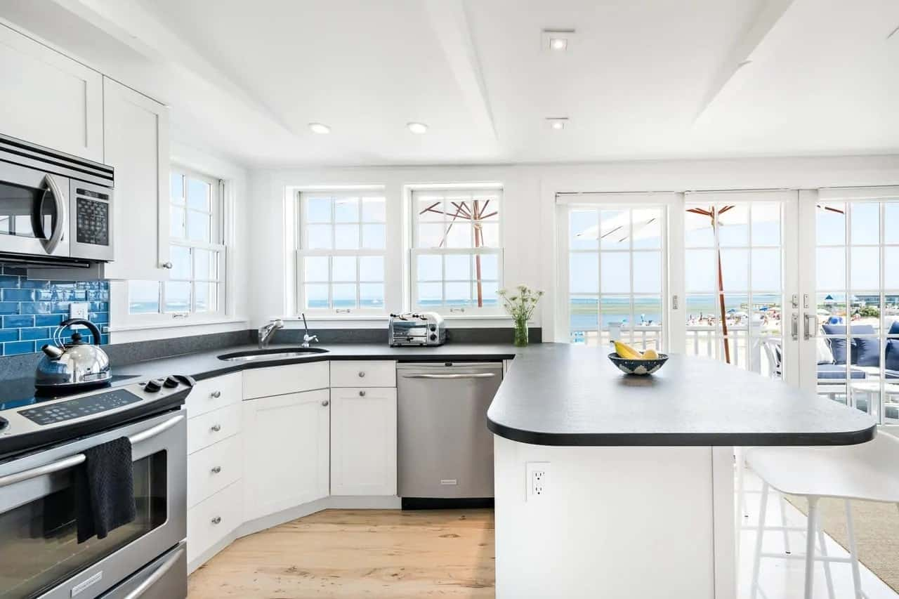This small Cottage-style kitchen makes up for its small light hardwood flooring with a U-shaped peninsula that has dark countertops and white cabinets that contrast the appliances. The surrounding glass windows and doors also serve to make the space appear bigger.