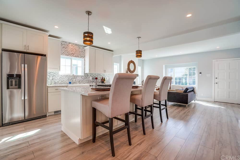 This charming Cottage-style kitchen hard flooring tiles that look like wood panels. This pairs well with the white kitchen island that has white shaker cabinets topped with white marble countertop and a couple of decorative pendant lights.