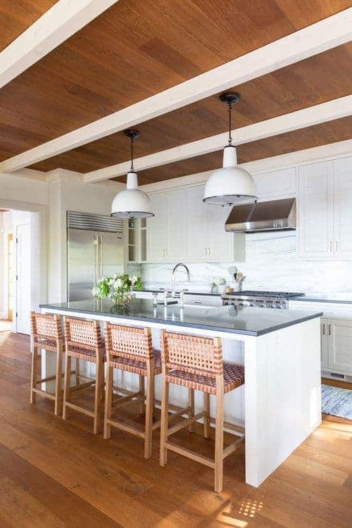 White beams provide a sleek contrast to the wood paneled ceiling mounted with dome pendant lights. This kitchen offers white cabinetry and a beadboard island bar lined with wicker counter stools.