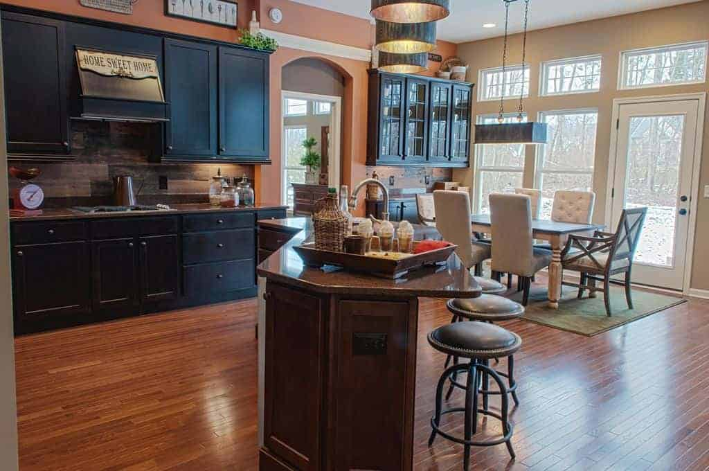 An eat-in kitchen with black cabinetry and a curved island bar lined with round bar stools and drum pendant lights. It includes a cozy dining set over a green area rug lighted by a linear chandelier.