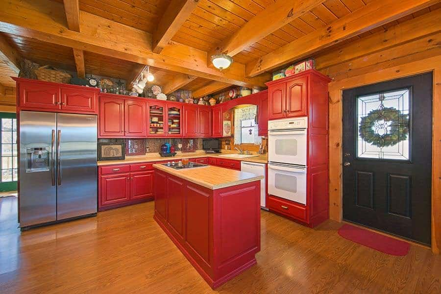 Country style kitchen boasts inset appliances and red cabinetry matching with the island bar that's topped with a wooden counter and built-in cooktop. It is illuminated by track lights and a flush light mounted on the wood beam ceiling.