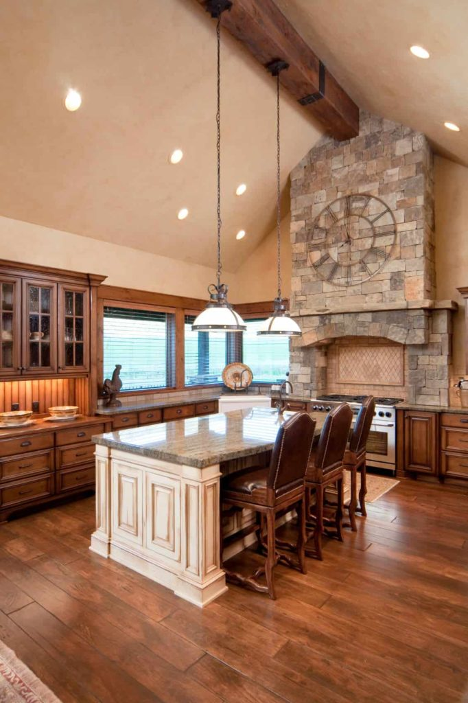 A brick cooking alcove and pillar add texture in this kitchen with wide plank flooring and a high cathedral ceiling lined with a large wood beam. It includes wooden cabinetry and white breakfast island lighted by glass dome pendants.