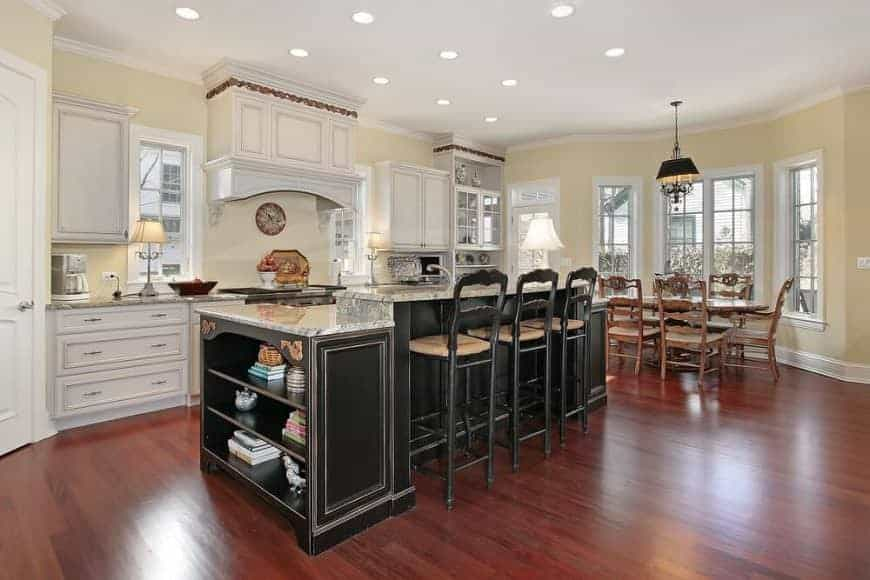 Black bar stools sit at a two-tier kitchen island that's topped with gray granite counters. It is contrasted by white cabinetry and range hood fixed against the light yellow wall.