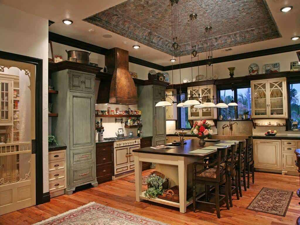 Country style kitchen with multi-colored cabinets and a white breakfast bar lined with cushioned counter chairs. It has rich hardwood flooring and a high tray ceiling mounted with recessed lights and glass dome pendants.
