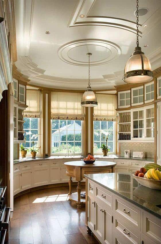 This kitchen boasts white and glass front cabinets along with a round island that blends in with the wide plank flooring. It is illuminated by glass dome pendants that hung from the tray ceiling.