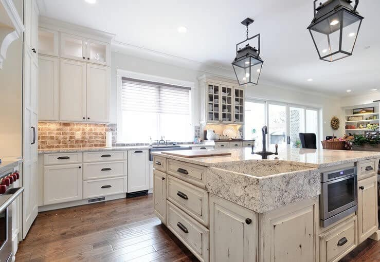Natural light flows in through the glazed windows in this kitchen with white cabinetry and a distressed island fitted with a farmhouse sink and iron fixtures. It is illuminated by lantern pendants and recessed ceiling lights.