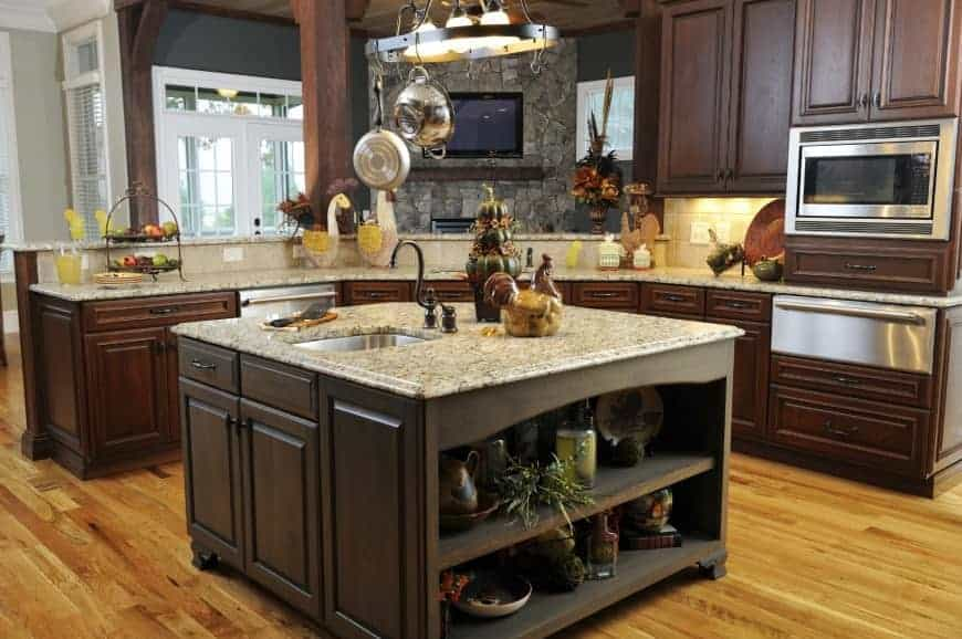 A wrought iron pot rack hangs over the granite top island with built-in storage and shelves. It is accompanied by wooden cabinets and stainless steel appliances.